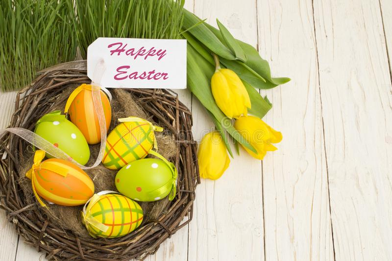复活节装饰用鸡蛋和郁金香在木背景 免版税库存图片