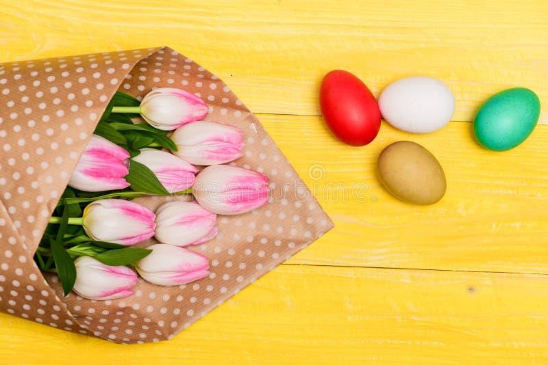 复活节震动 春天假日 愉快的复活节季节 收集复活节彩蛋 五颜六色的鸡蛋和花束新鲜的郁金香花 免版税库存照片