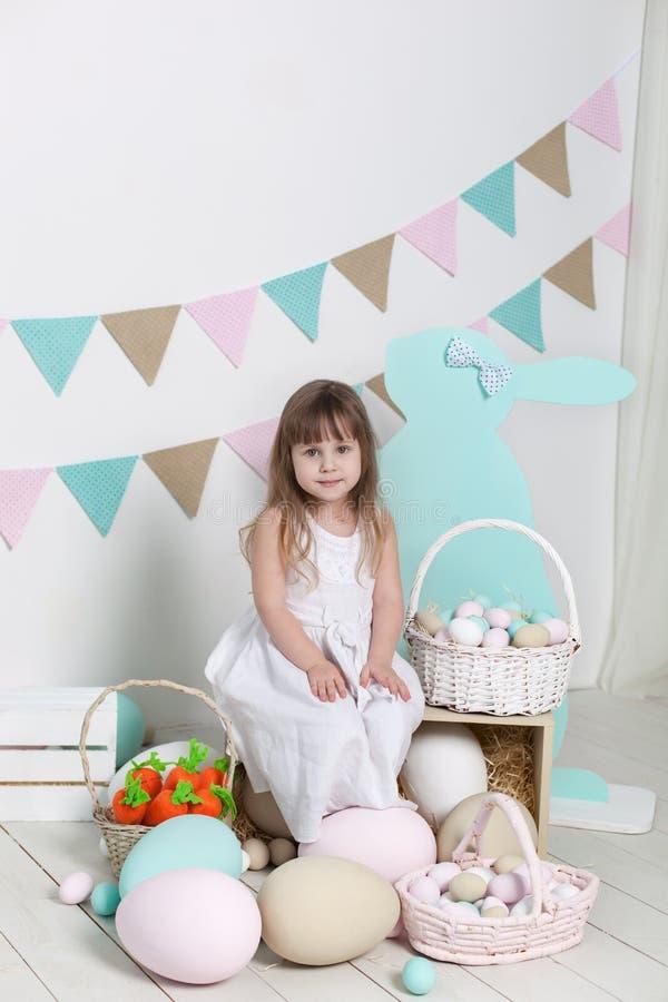 复活节!一件白色礼服的一女孩在一个篮子附近坐用鸡蛋和复活节兔子 复活节地点,装饰 Famil 免版税库存图片