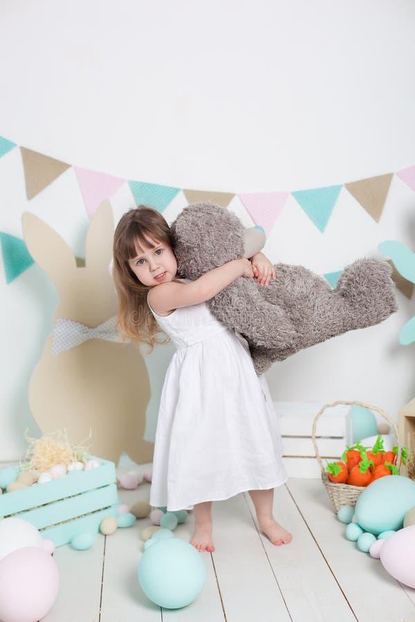 复活节!一件白色礼服的一美丽的女孩拥抱一个大玩具熊 许多不同的五颜六色的复活节彩蛋,五颜六色的interi 免版税库存图片