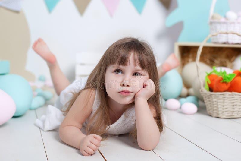 复活节!一美丽的女孩的面孔的特写镜头画象 许多不同的五颜六色的复活节彩蛋,五颜六色的复活节内部 r 库存图片