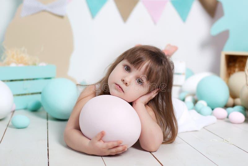 复活节!一美丽的女孩的面孔的特写镜头画象 许多不同的五颜六色的复活节彩蛋,五颜六色的复活节内部 r 图库摄影