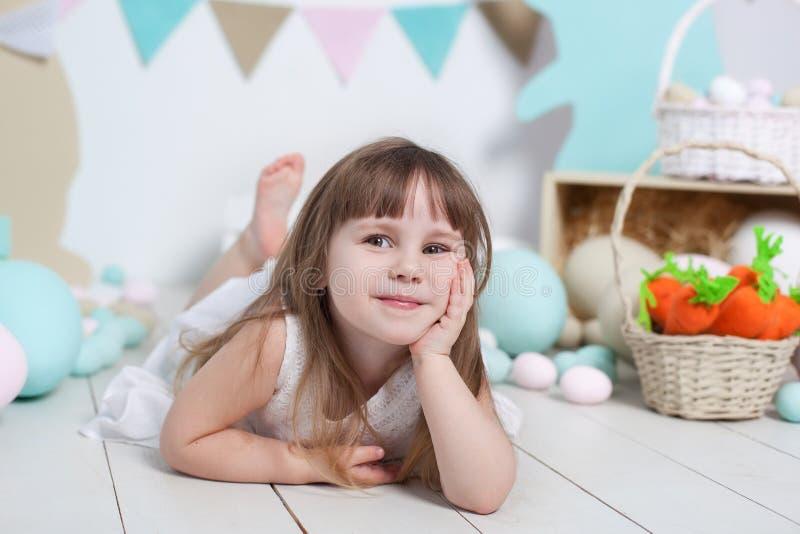 复活节!一美丽的女孩的面孔的画象 许多不同的五颜六色的复活节彩蛋,五颜六色的内部 复活节兔子,红萝卜a 免版税库存照片