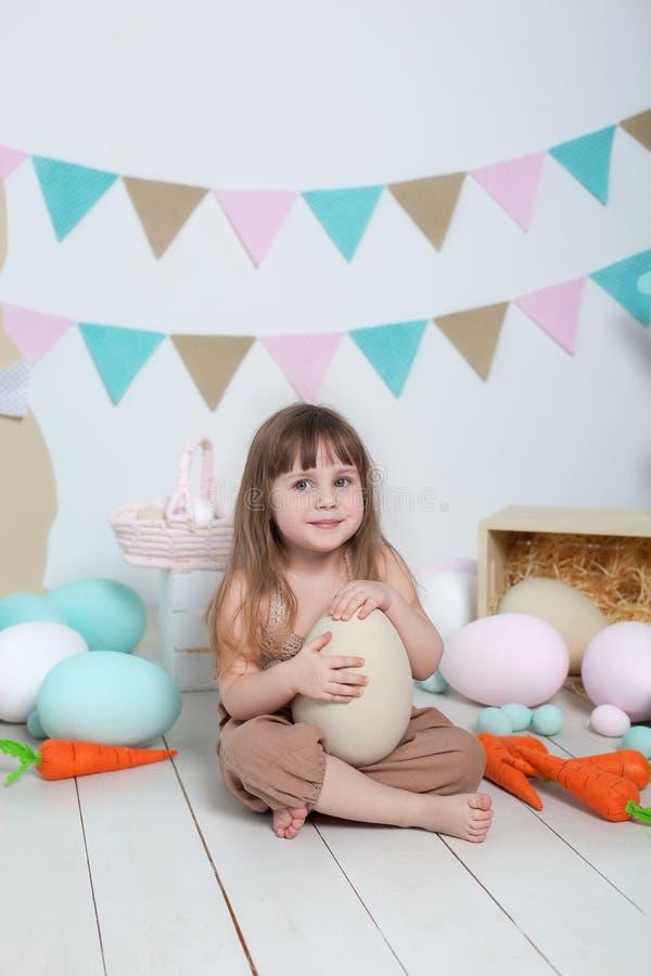 复活节!白色背景的美丽的女孩用复活节五颜六色的鸡蛋、复活节篮子和野兔 复活节地点,decoratio 免版税库存照片