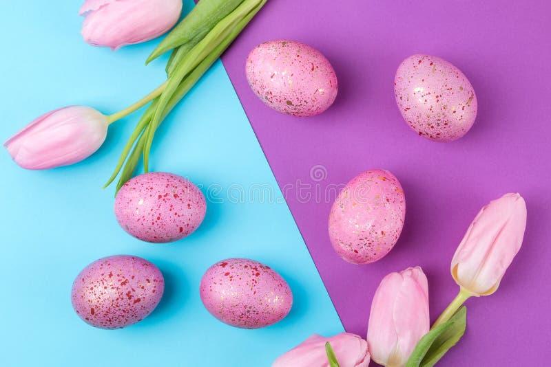 复活节 桃红色复活节彩蛋和花郁金香在时髦丁香和蓝色背景 愉快的复活节 节假日 在视图之上 免版税图库摄影