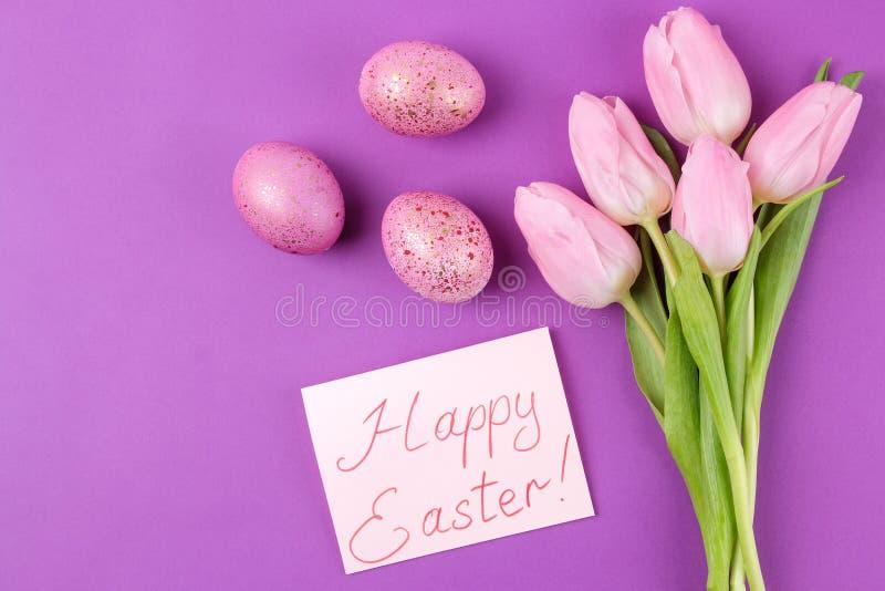 复活节 桃红色复活节彩蛋和花郁金香在时髦紫色背景 愉快的复活节 节假日 顶视图 免版税库存图片