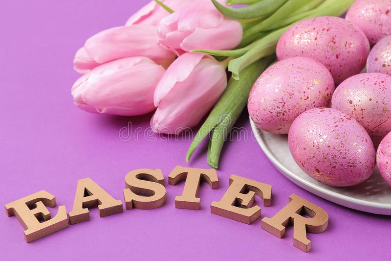 复活节 桃红色复活节彩蛋和花郁金香在时髦紫色背景 愉快的复活节 节假日 库存图片