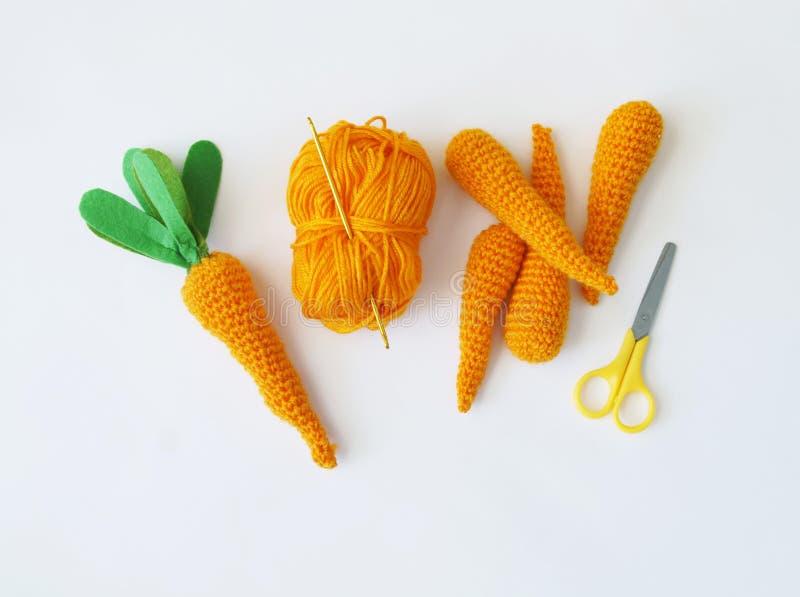 复活节 被编织的红萝卜玩具 创造红萝卜的过程 橙色线程数 免版税库存图片