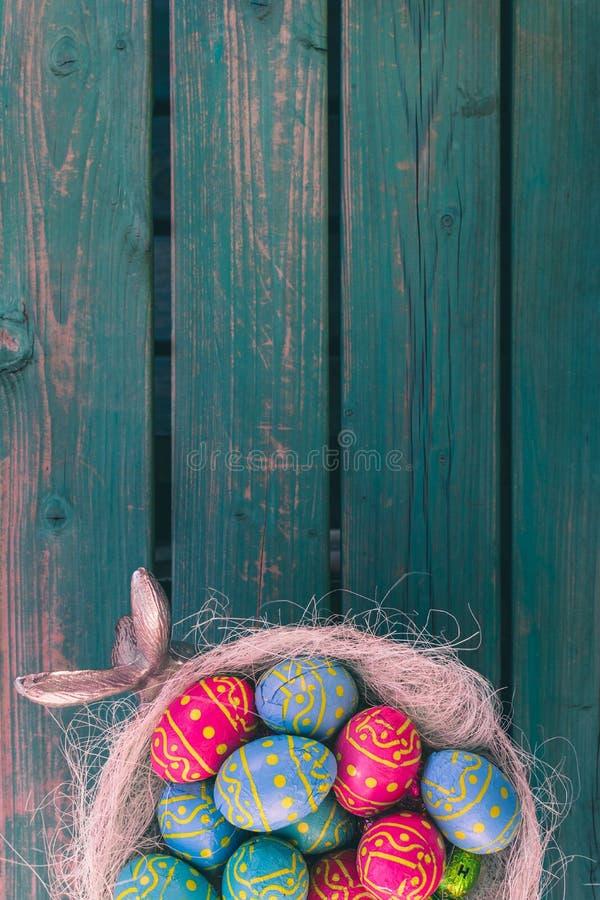复活节choclate鸡蛋,酯类碗,绿色长凳,复活节背景 库存照片