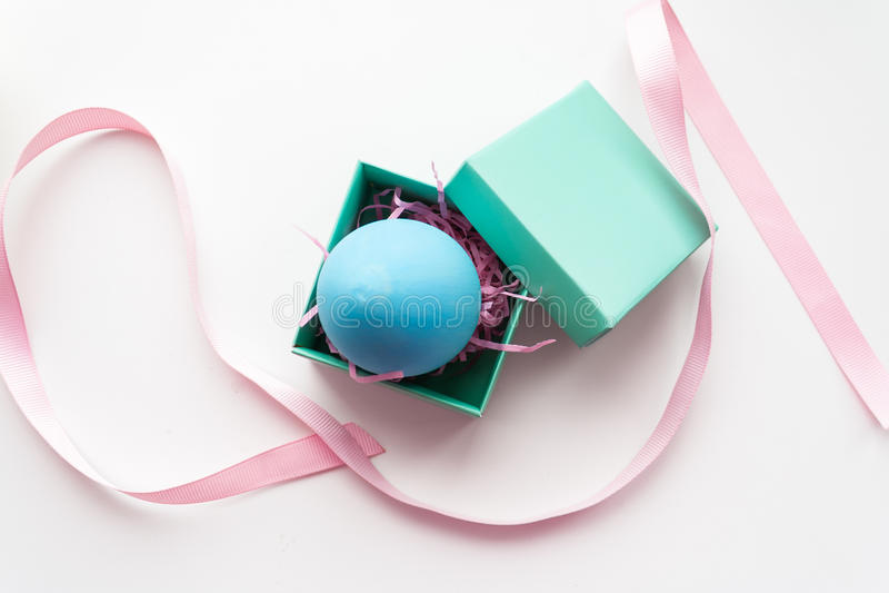 复活节、蓝色鸡蛋在礼物盒和桃红色丝带在白色背景 免版税库存图片