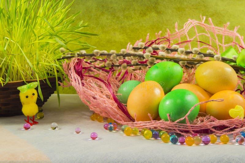 复活节上色了鸡蛋和杨柳在桌上,选择聚焦 免版税库存照片
