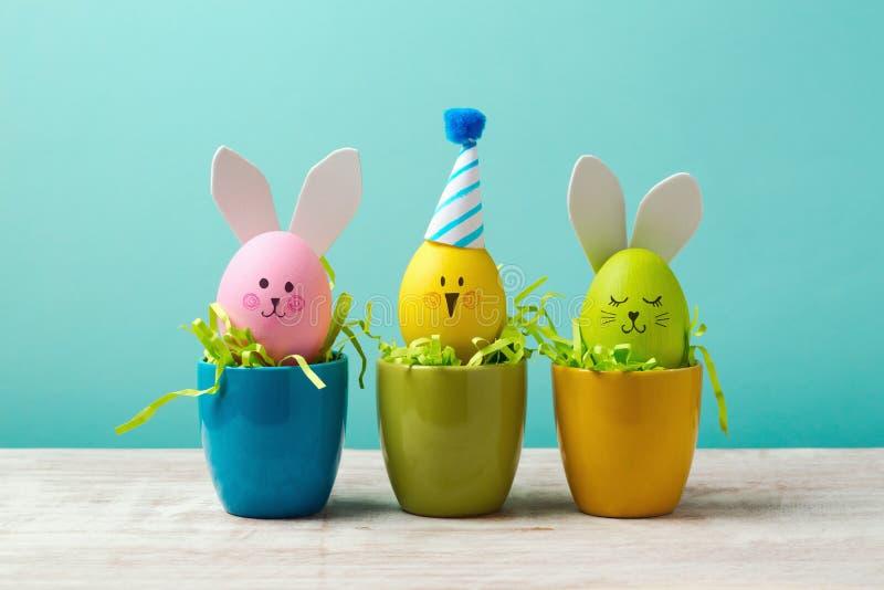 复活节假日概念用逗人喜爱的手工制造鸡蛋、兔宝宝、小鸡和党帽子在杯子 库存图片