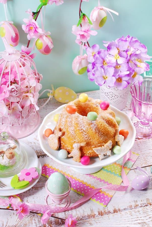 复活节圆环蛋糕用糖果鸡蛋和曲奇饼在春天桌上 免版税库存图片