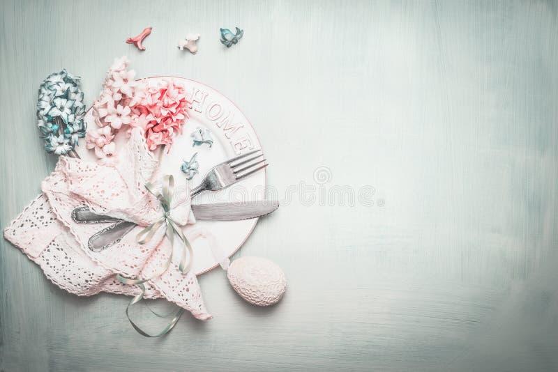 复活节在蓝色桃红色淡色的桌设置与可爱的花和装饰怂恿,顶视图 免版税库存图片