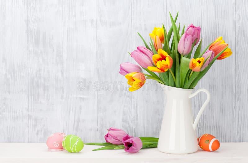 复活节彩蛋和五颜六色的郁金香花束 免版税库存照片
