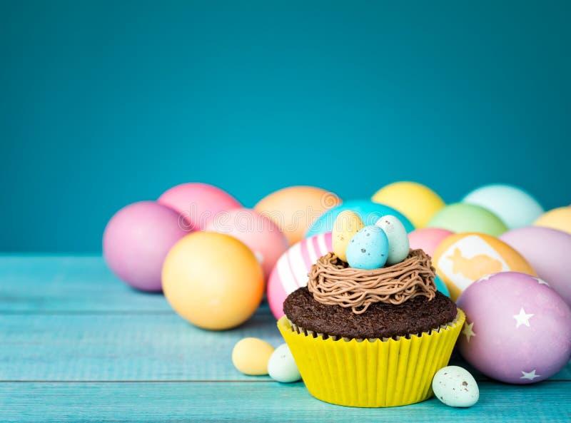 复活节彩蛋和杯形蛋糕 免版税图库摄影