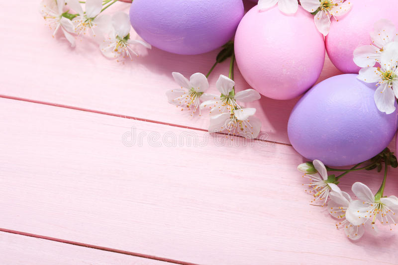 复活节彩蛋和白花在桃红色桌上 免版税库存图片