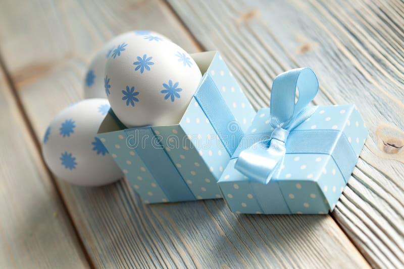 复活节彩蛋和礼物盒在木桌上 库存照片