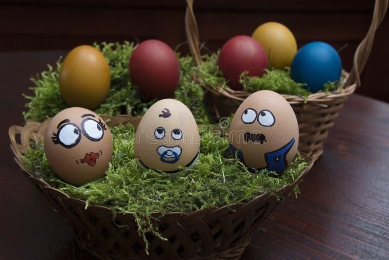 复活节彩蛋在柳条筐的面孔家庭 免版税库存照片