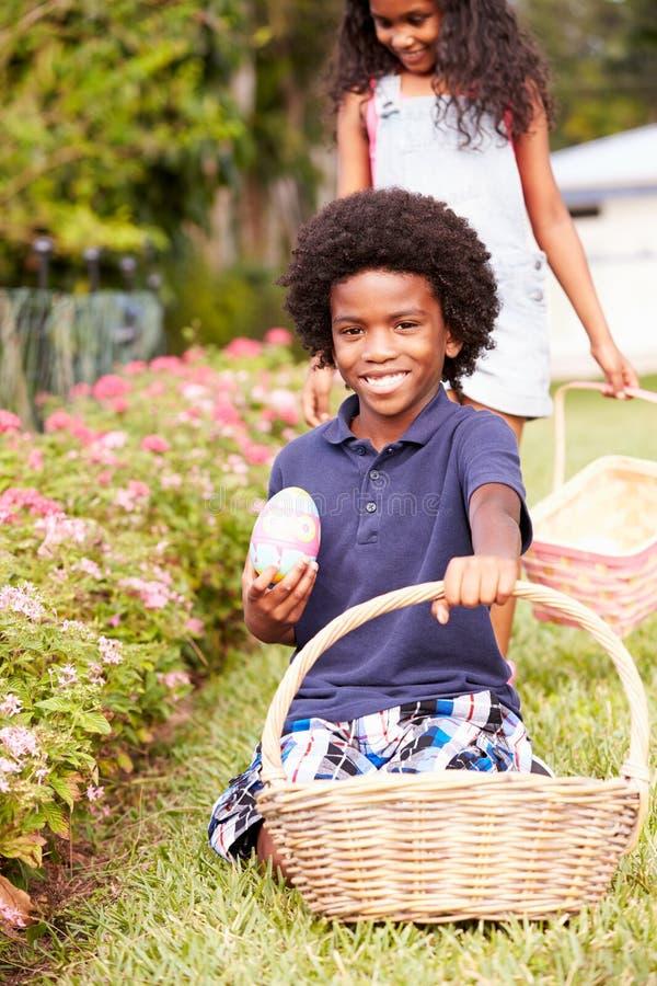 复活节彩蛋狩猎的两个孩子在庭院里 免版税库存图片