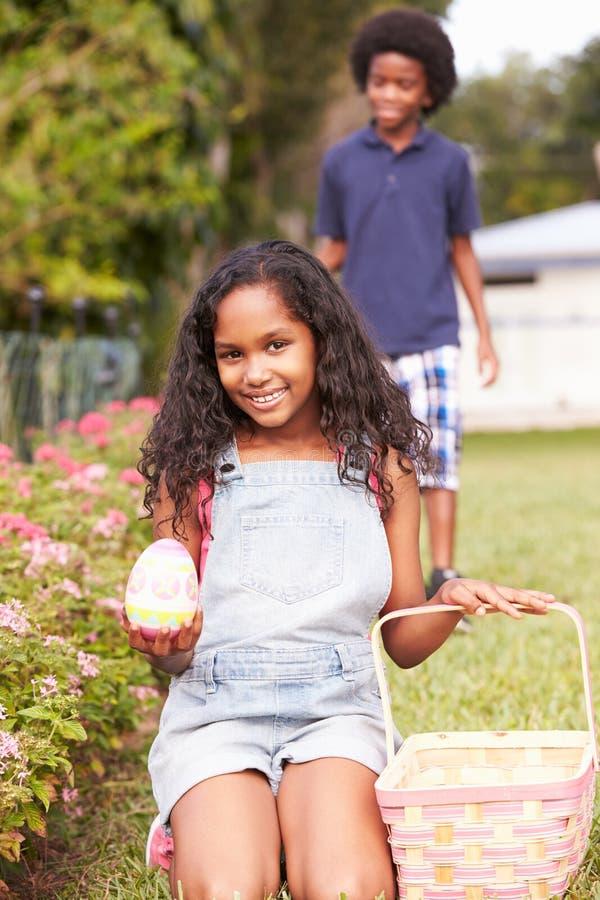 复活节彩蛋狩猎的两个孩子在庭院里 免版税图库摄影