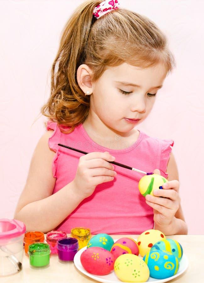 绘复活节彩蛋的逗人喜爱的小女孩 库存图片