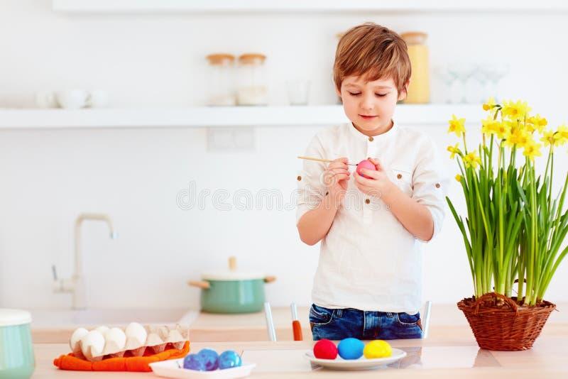 绘复活节彩蛋的逗人喜爱的愉快的孩子在厨房书桌 库存图片
