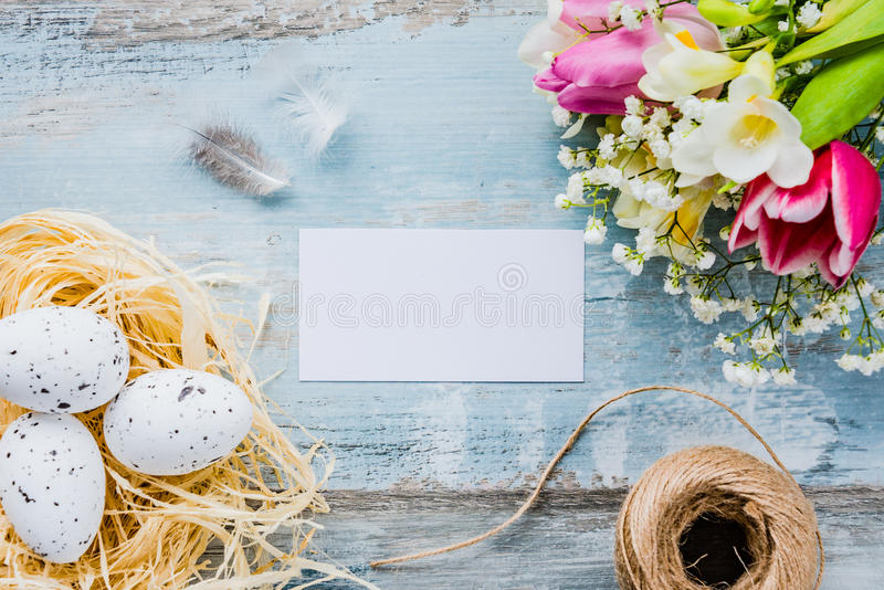 复活节彩蛋顶视图在巢春天开花并且用羽毛装饰在蓝色土气木背景 空的看板卡 免版税库存图片