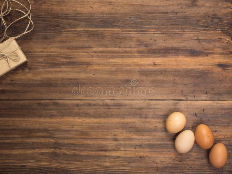 复活节彩蛋,在老木桌上的礼物盒从板条 与空间的顶视图您的设计,复活节问候的或者 库存图片
