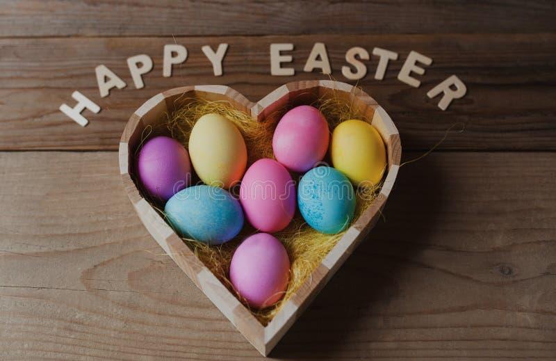 复活节快乐-在一个心形的碗的色的鸡蛋 图库摄影