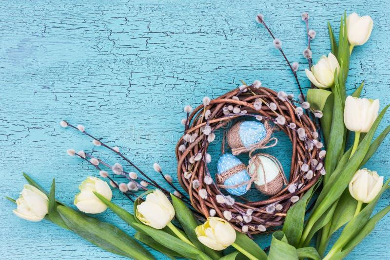 复活节杨柳花圈、白色郁金香和蓝色复活节彩蛋在蓝色背景 免版税库存照片
