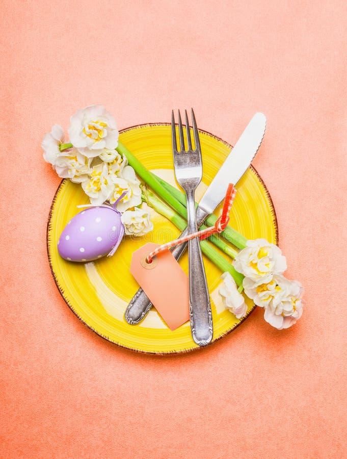 复活节桌与黄水仙花的餐位餐具,利器,板材,鸡蛋和倒空在粉红彩笔背景,顶视图的标签卡片 图库摄影