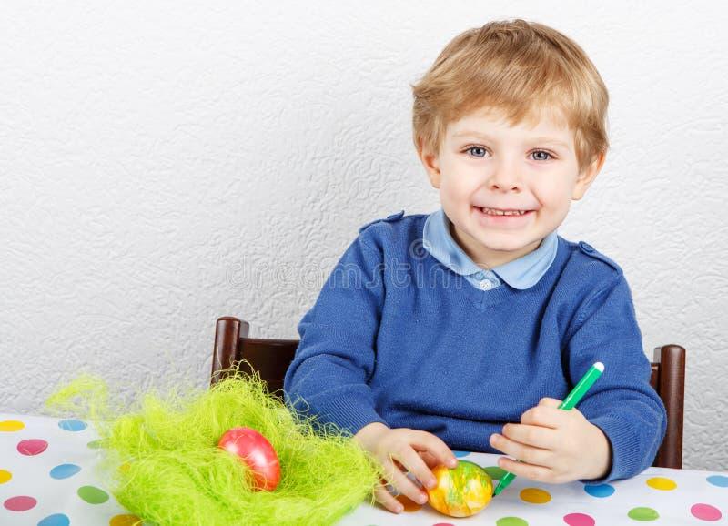 绘复活节狩猎的小小孩男孩五颜六色的鸡蛋 免版税库存照片