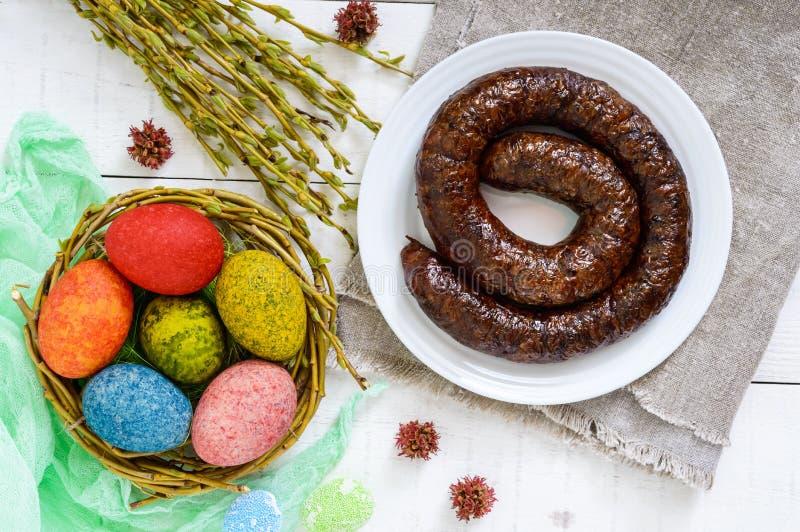 复活节盘:五颜六色的色的鸡蛋,自创香肠圆环,杨柳枝杈 库存图片