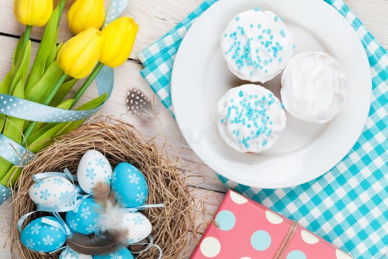 复活节背景用在巢,黄色郁金香的蓝色和白鸡蛋 库存图片