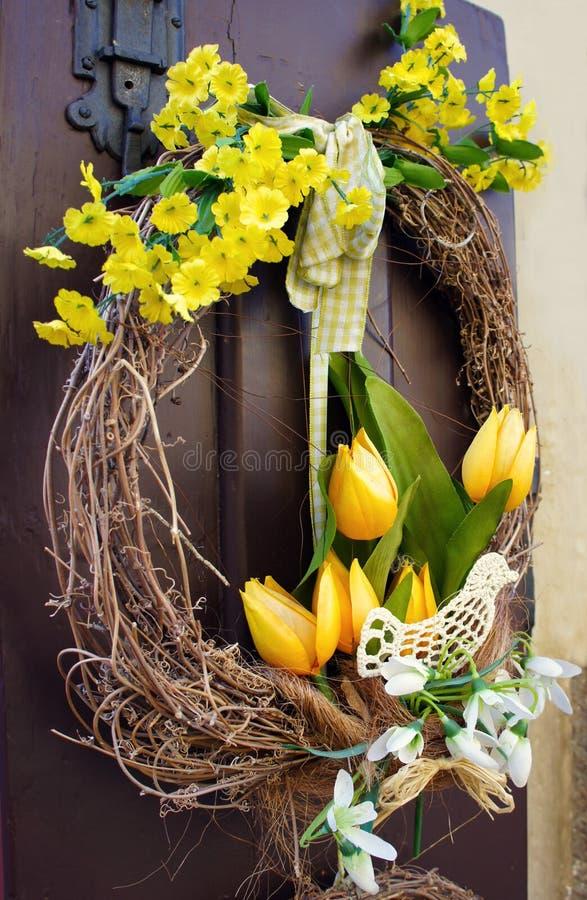 复活节花圈 在房子的木门的春天装饰 免版税库存图片
