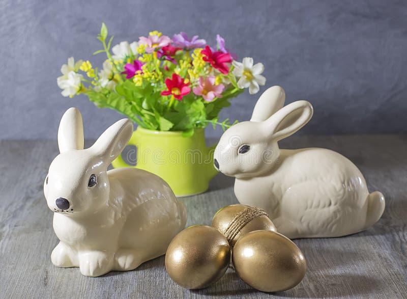复活节装饰兔子、金黄鸡蛋和花 免版税图库摄影