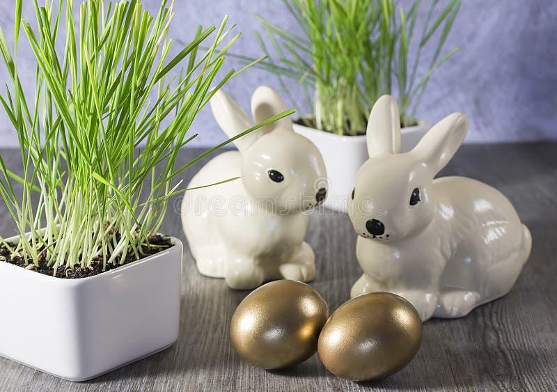 复活节装饰兔子和金黄鸡蛋在灰色木后面 免版税库存照片