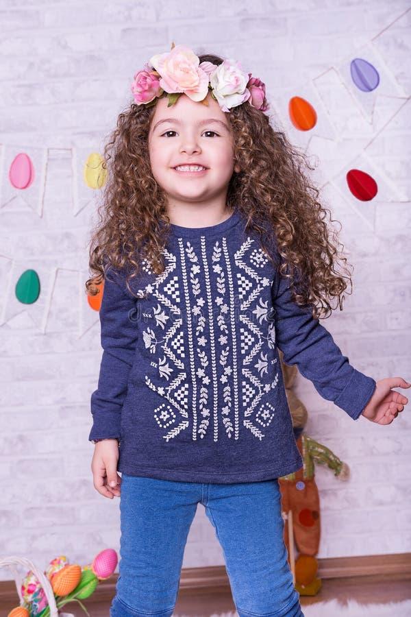 复活节装饰的逗人喜爱的矮小的甜女孩在家 库存图片
