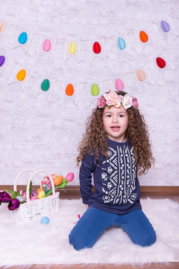 复活节装饰的逗人喜爱的矮小的甜女孩在家 免版税库存照片