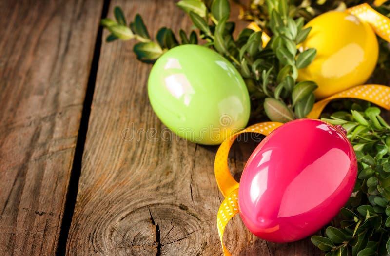 复活节装饰-与黄杨属的鸡蛋在木头 免版税图库摄影