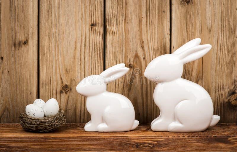 复活节装饰-陶瓷复活节兔子和巢用鸡蛋 免版税库存图片