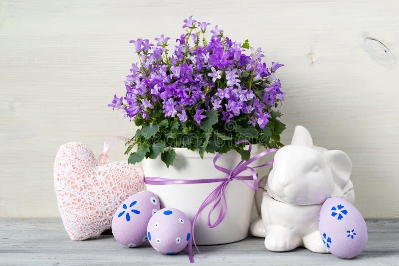 复活节设计用复活节彩蛋和一个罐在白色木背景的花 免版税库存照片