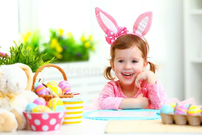 复活节 有兔宝宝耳朵的愉快的儿童女孩用色的鸡蛋和f 库存图片
