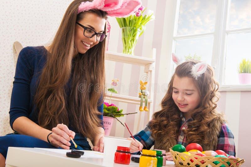 复活节-母亲和女儿油漆鸡蛋,兔宝宝耳朵 免版税库存图片