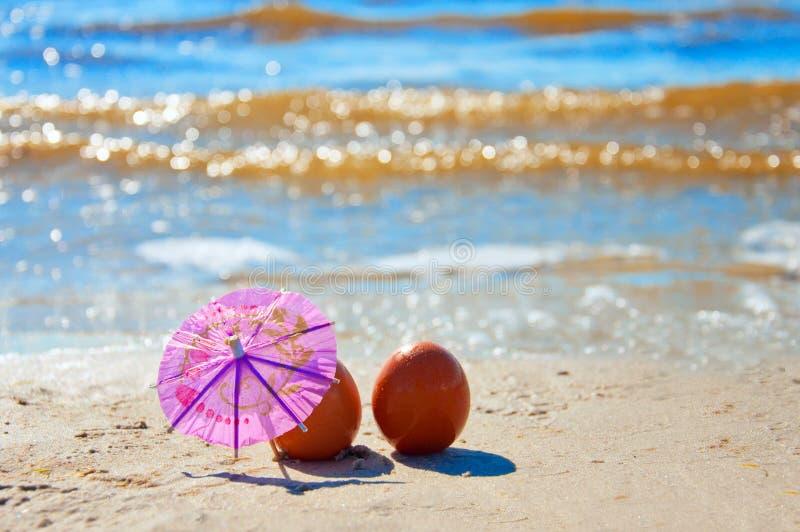 复活节滑稽的鸡蛋在海滩的伞下 免版税图库摄影