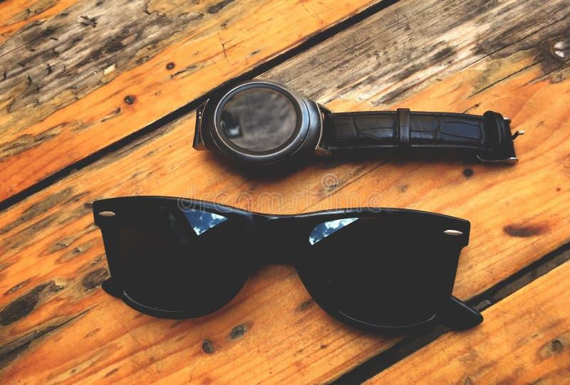 夏令时、强的葡萄酒玻璃和一块巧妙的手表,在葡萄酒木背景 库存照片