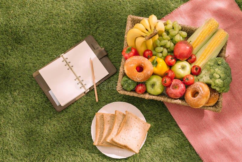 夏令时在草的野餐设置用开放野餐篮子、果子、沙拉和樱桃饼 库存照片