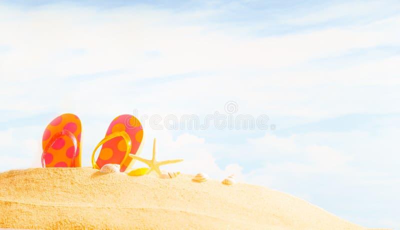 夏令时季节、五颜六色的多斑点的凉鞋或者啪嗒啪嗒的响声在沙滩有晴朗的五颜六色的蓝天背景和拷贝空间 免版税图库摄影