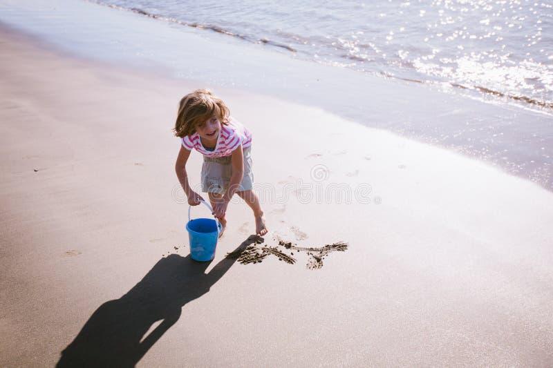 夏令时:在海滩的微笑的女孩戏剧 免版税库存图片
